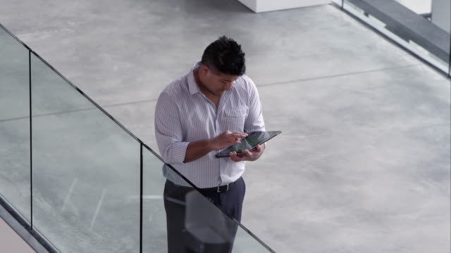 panning view of man talking to another person while looking at tablet. - guardare verso il basso video stock e b–roll