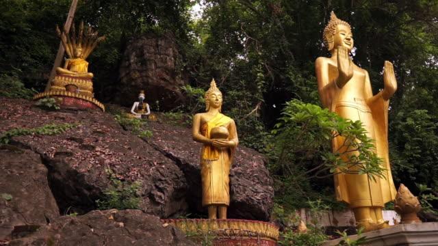 panning view of many buddha statues on mount phousi, luang prabang, laos - mudra stock videos & royalty-free footage