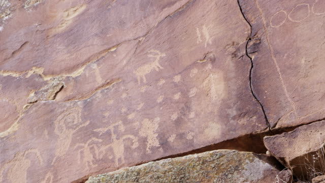 vídeos de stock, filmes e b-roll de panning view of petroglyph carvings across cliff in nine mile canyon - anasazi