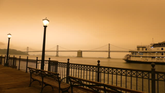 panning view of pier at fisherman's wharf street lamps on with the bay bridge and treasure island in the distance under the orange sky on september 9... - fisherman's wharf san francisco stock videos & royalty-free footage