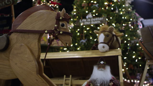 panning view of rocking horse in front of christmas decor - spielzeug stock-videos und b-roll-filmmaterial