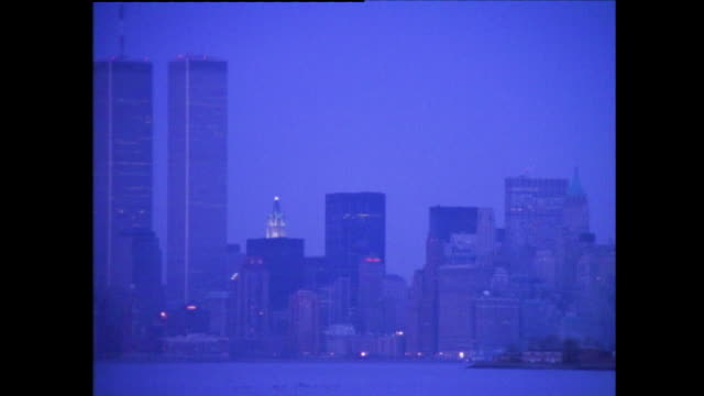 panning view of statue of liberty, twin towers/world trade center, and new york city skyline under the blueish evening light - skyline stock videos & royalty-free footage