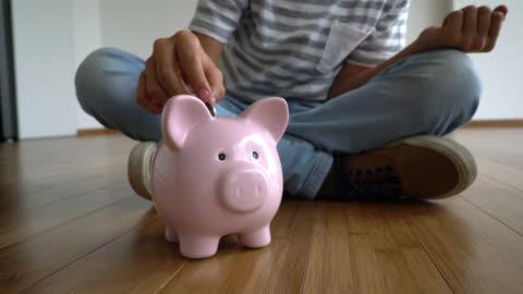 stockvideo's en b-roll-footage met weergave van onherkenbaar kind munten ingebruikneming een spaarpot pannen - economie