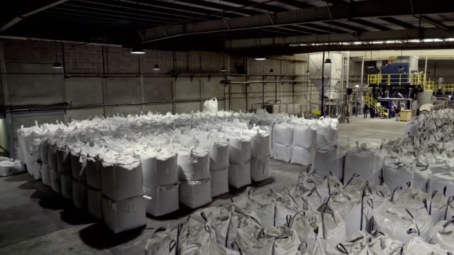 panning view of warehouse with sacks of pet crushed flakes for a recycling  plastic industry - bale stock videos & royalty-free footage
