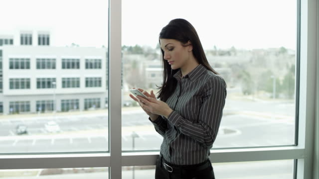 Panning view of woman answering smartphone in front of windows.