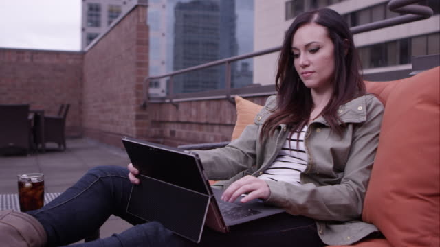 Panning view of woman relaxing on roof top using laptop.