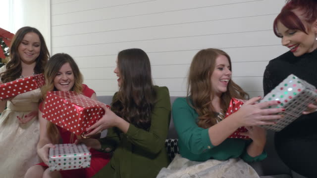 panning view of women exchanging gifts on couch - swap stock videos and b-roll footage