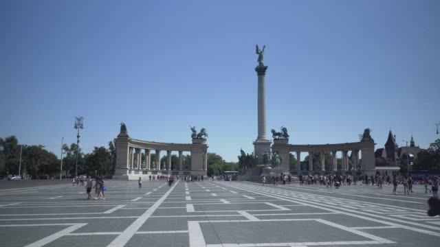 panning view on national landmark: heroes square, architectural column, and monument, along with a group of traveler in budapest from on a sunny weekend day of summer and blue sky, hungary. - traditionally hungarian stock videos & royalty-free footage
