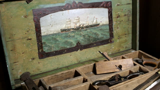 panning view over old tools in chest with painting of boat - hand saw stock videos and b-roll footage