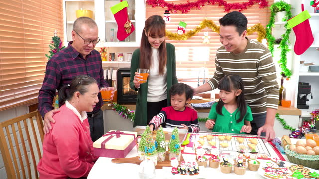 panning view: sohn aufgeregt, lebkuchenkeks mit südostasiatischem mehrgenerationen-familientreffen zu großeltern, großvater, großmutter, weihnachtsdessert, lebkuchenkeks, weihnachtsbaum-cupcake in der küche für die weihnachtsfeier vorzubereiten - 35 39 years stock-videos und b-roll-filmmaterial