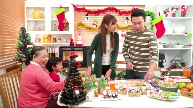 panning view: junge familie mit zwei kindern wiedersehen zu großeltern, großvater, großmutter, bereiten sie weihnachtsdessert, lebkuchenkeks, weihnachtsbaum cupcake in der küche für die weihnachtsfeier zu , südostasiatische mehrgenerationenfamilie - 35 39 years stock-videos und b-roll-filmmaterial