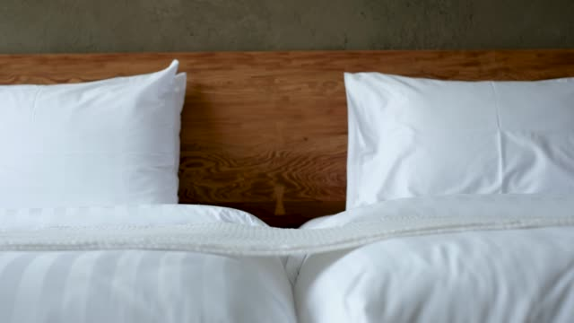 panning white pillow on bed in bedroom. - pillow stock videos and b-roll footage