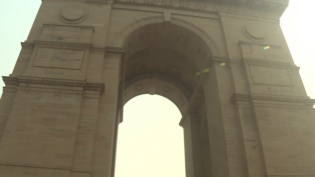 Panning wide shot of Prince Charles and Camilla Duchess of Cornwall paying respects at India Gate New Delhi as the Last Post is played