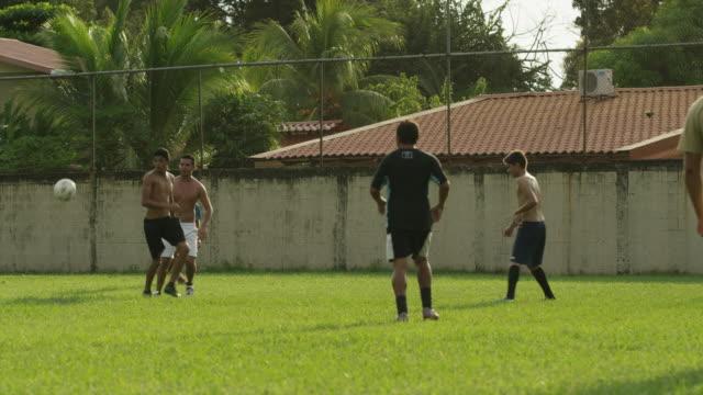 panning wide shot of soccer teams playing on field / esterillos, puntarenas, costa rica - puntarenas stock-videos und b-roll-filmmaterial