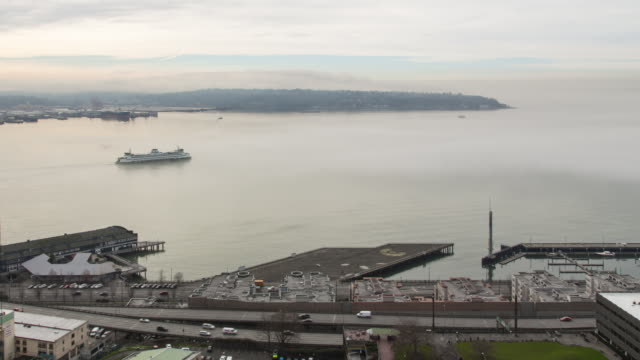 A panning winter daytime time lapse of a ferry leaving Coleman Dock (Seattle, WA) and disappearing into fog rolling into Elliott Bay
