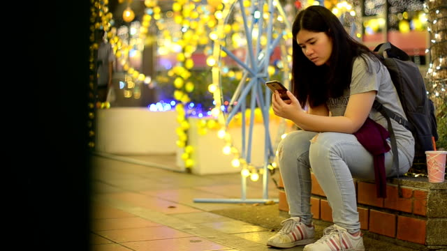 panning: Woman concentrate on using smartphone in celebration event at night