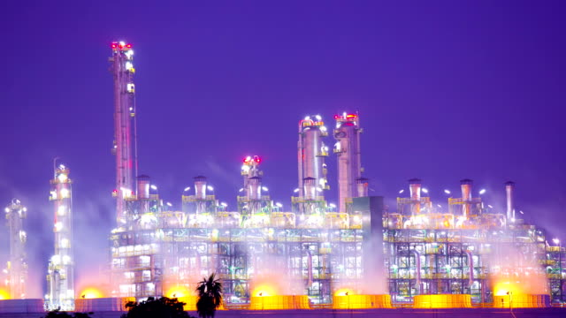 Panning Working of Oil Refinery Plant at Night Zoom Out