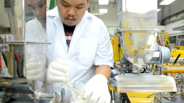panorering: unga och stora ingenjör Häll plastpärlor i extruder maskin