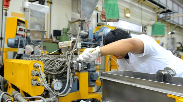 panorering: ung ingenjör koncentrerar sig till ren dör av extruder maskin