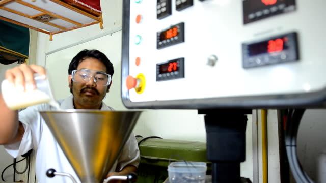 panorering: ung ingenjör Häll plastpärlor i extruder maskin