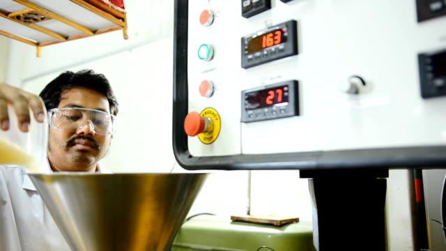 panorering: ung ingenjör Häll plastpärlor i hopper