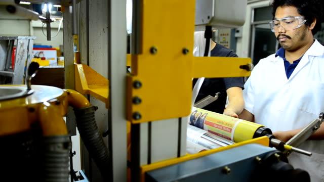panorering: ung ingenjör sätta en gummi rulle för att hålla plastpåse fiilm
