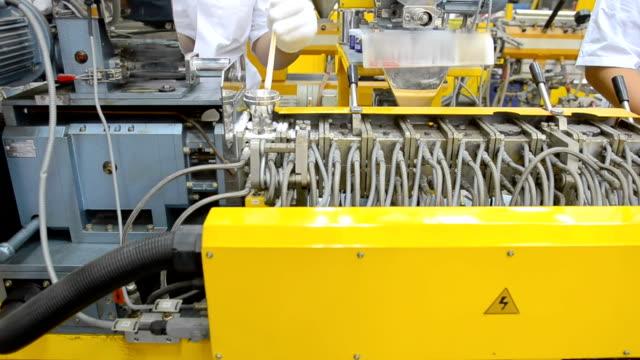 panorering: ung ingenjör använda träpinne för att pärla flyta in i extruder maskin