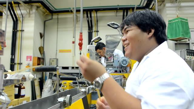 panorering: unga ingenjörer med twin skruv extruder machine
