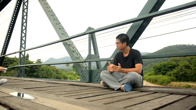 panning: young man sit leisurely on a history bridge - mae hong son province stock videos and b-roll footage
