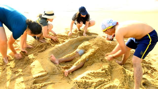 stockvideo's en b-roll-footage met pannen: jongeren schimmel sandman op hun vriend - digging