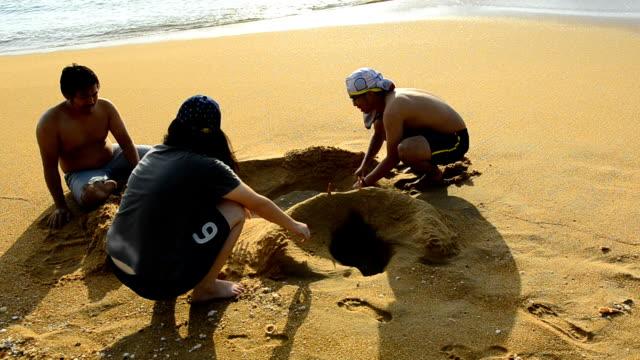 panorering: ungdomar spela sand på stranden