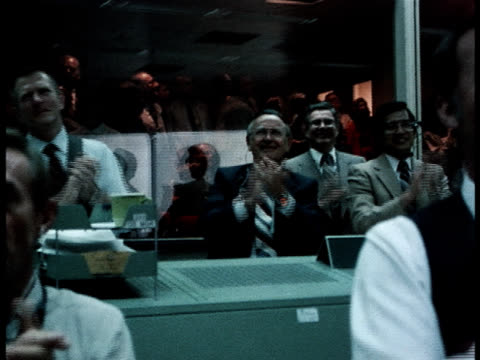 Panning-shot of Houston NASA workers applauding a successful mission.