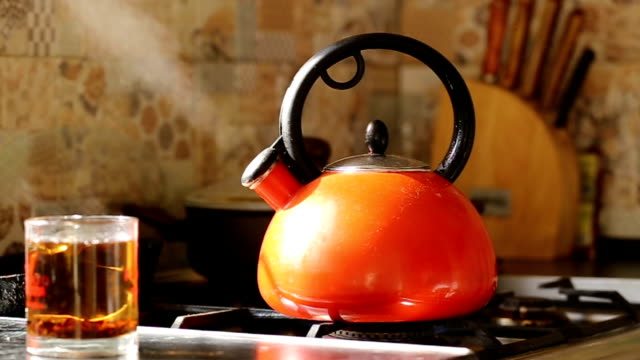 panorama along the kettle which boils on the gas stove. - stove stock videos & royalty-free footage