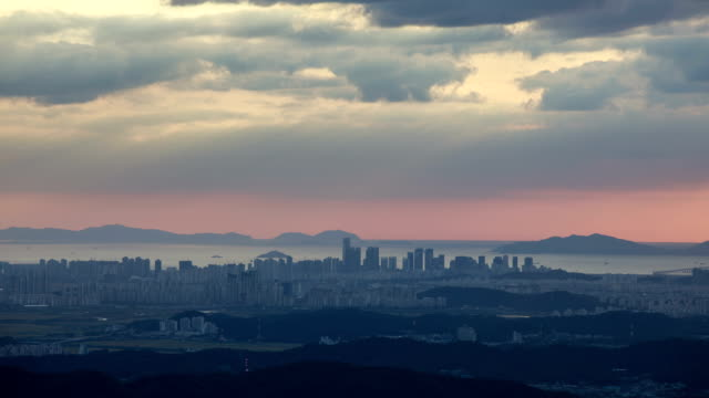 panorama of songdo international business district with crepuscular rays - dramatischer himmel stock-videos und b-roll-filmmaterial