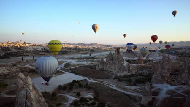 panorama shot of hot air balloons preparing to rise from basalt rocks - cappadocia, turkey - basalt stock videos & royalty-free footage