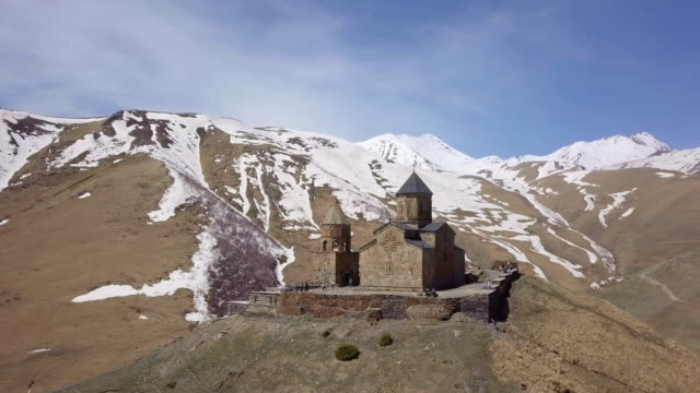 panoramic aerial 4k /gergeti trinity church, kazbegi mountain, georgia - religious symbol stock videos & royalty-free footage
