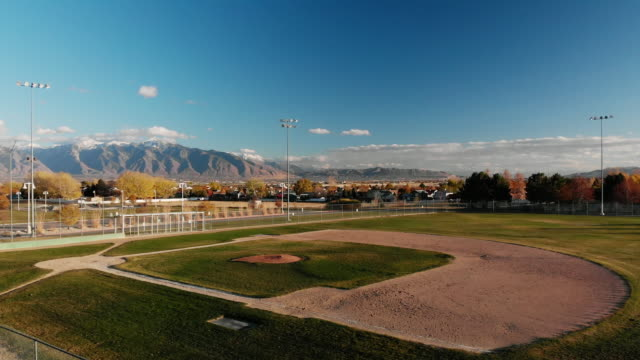 panoramic aerial drone shot of an american flag waving in the breeze, empty baseball field/diamond, the wasatch mountains, and salt lake city at sunset/sunrise - panoramic stock videos & royalty-free footage
