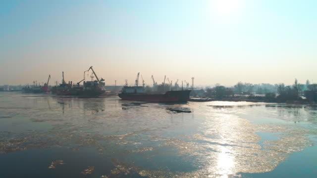 Aerial Panoramablick auf den Industriehafen mit kommerziellen Schiffen und Containern im Winter.