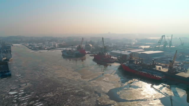 Panoramic aerial view on the industrial port with commercial ships and cargo containers in winter.