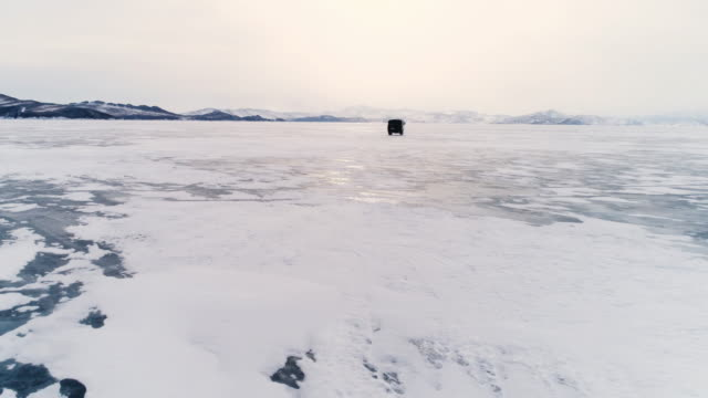 panoramic flight around an off-road vehicle over the open frozen space of the deep-water lake baikal in the winter. - frozen water stock videos & royalty-free footage