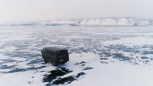 vídeos de stock e filmes b-roll de panoramic flight around an off-road vehicle over the open frozen space of the deep-water lake baikal in the winter. - rússia