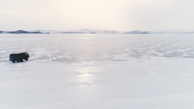 Panoramic flight around an off-road vehicle over the open frozen space of the deep-water Lake Baikal in the winter.