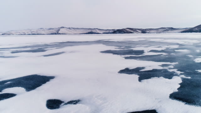 panoramic flight through the open frozen space of the deep-water lake baikal in winter. - frozen water stock videos & royalty-free footage