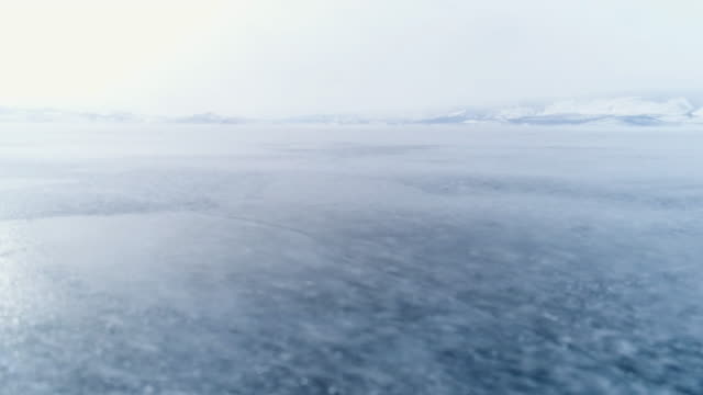 panoramic flight through the open frozen space of the deep-water lake baikal in winter. - 吹雪点の映像素材/bロール