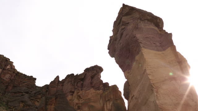 a panoramic landscape of smith rock state park on a sunny day with a colorful sunset. - smith rock state park stock videos & royalty-free footage