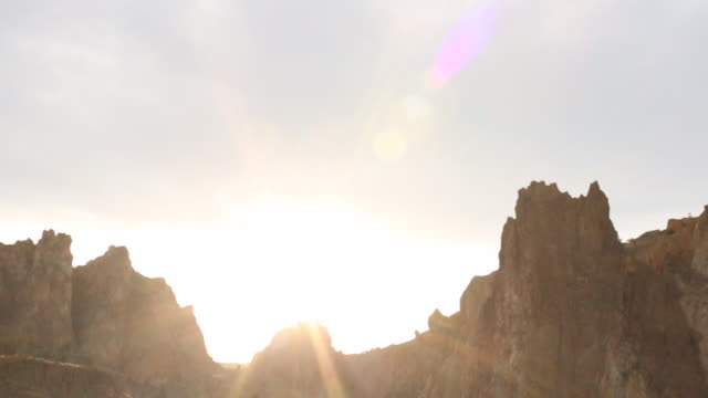 A panoramic landscape of Smith Rock State Park on a sunny day with a colorful sunset.
