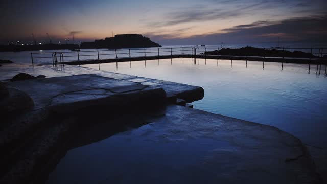 panoramic landscape view of an outdoor swimming pool, in the coastline of guernsey, at dusk - channel islands england stock videos & royalty-free footage