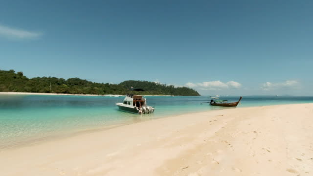 vidéos et rushes de panoramic of speedboat and thai longtail boat moored in perfect shallow tropical island lagoon - lagon