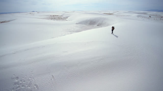 Panoramic scenic aerial video with the camera flying around the young Caucasian man, tourist - hiker with the big backpack, walking through the sandy desert. White Sands National Monument, New Mexico, USA.  Aerial drone footage.