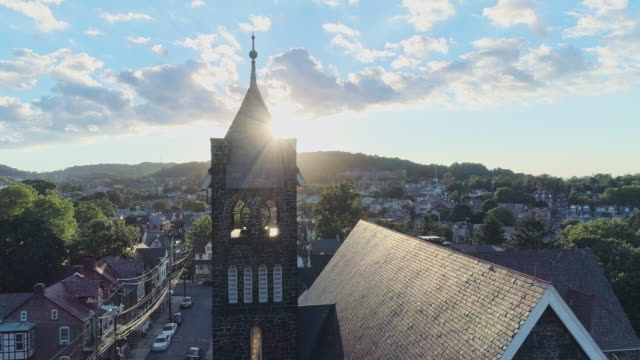 panoramic scenic view of bethlehem, pennsylvania, at sunset. fritz memorial united methodist church. aerial drone video with the panoramic camera motion, with the tower passing in front of the sun. - protestantism stock videos & royalty-free footage